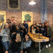 More than a dozen employees around a table at a brewery